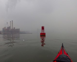 We paddle to the red buoy in the middle of the East River