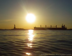 A bulk carrier passes down the harbor in the evening sun